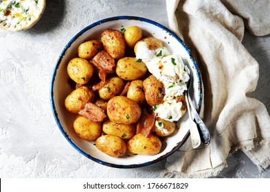 Baked young potatoes with bacon and sour cream sauce on a gray background, still life