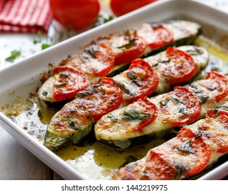Baked zucchini with the addition of tomatoes, mozzarella cheese, herbs and olive oil (caprese salad) in a ceramic baking dish, close-up. Nutritious and tasty vegetarian dish