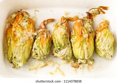 baked zucchini or courgette flowers with parmesan cheese in a casserole dish, italian appetizer, selected focus, narrow depth of field