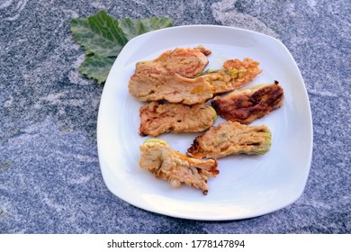 Baked zucchini flowers on white plate