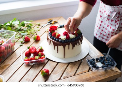 Baker adding blueberries to a cake