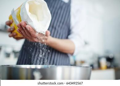Baker adding flour in bowl to make dough