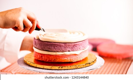 Baker assembling pink and purple cake layer to make unicorn cake for little girl's birthday party.