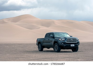 Baker, CA/USA - March 3, 2020: Toyota Tacoma TRD Off-Road medium body truck. Metallic grey color. Photographed at Dumont Dunes in Mojave Desert