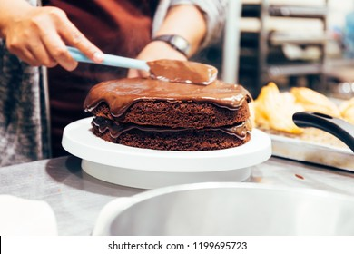 Baker chef preparing moist and spatula dark chocolate torte cake and putting the top with cocoa cream mixed together in kitchen in bakery shop