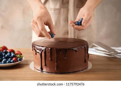 Baker decorating fresh delicious homemade chocolate cake with berries on table, closeup