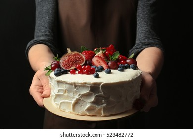 Baker hands holding delicious creamy cake closeup