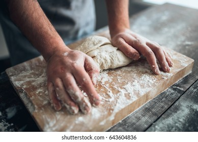 Baker hands kneading the dough with flour