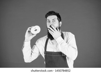 baker hold donut. Funny hipster. Bearded man cook. Chef man in cafe. Diet and healthy food. Bearded man eat doughnut. Calorie. Feel hunger. Bearded chef. Bearded man in apron. Do you want a bite.