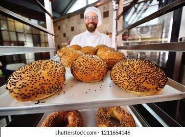 Baker holding a tray with round rolls for burgers with black sesame on the background of a bakery or bread factory