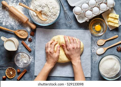 Baker knead dough bread, pizza or pie recipe ingridients with hands, food flat lay on kitchen table background. Working with butter, milk, yeast, flour, eggs, sugar pastry or bakery cooking.