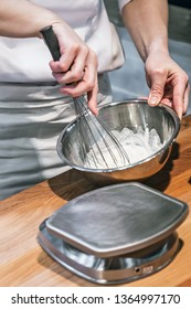 the Baker kneads the dough and mixes it with a whisk in the kitchen