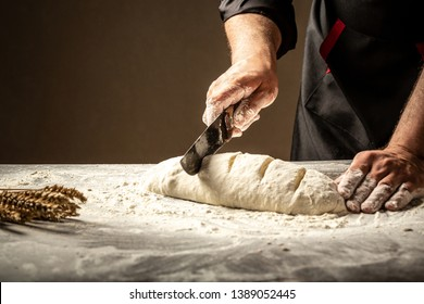 Baker making patterns on raw bread using a knife to shape the dough prior to baking. Manufacturing process of spanish bread. Food concept.