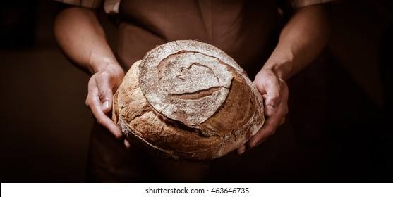 Baker man holding a beautiful round bread