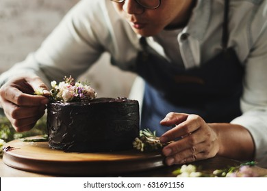 Baker Man Using Flowers Decorating Chocolate Cake