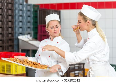 Baker nibbling fresh pastry from tray in bakery