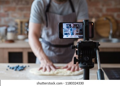 baker online courses. food preparing and culinary training class concept. smiling bearded chef kneading dough in the kitchen and shooting video of himself using mobile phone on a tripod.