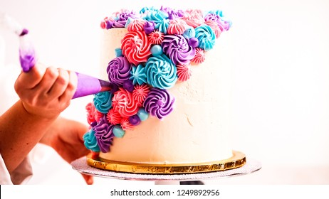 Baker piping pastel color buttercream rosettes on a white cake to make a unicorn cake.