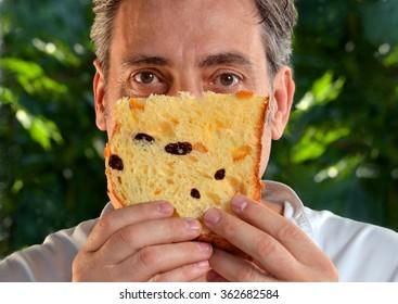 Baker portrait eating and tasting fresh panettone slice, eating panettone.