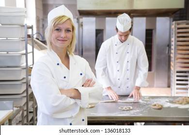 Baker posing in bakery or bakehouse. Another baker is working in the background
