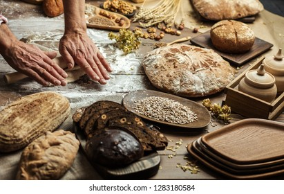 Baker prepares bread, rolls the dough with a wooden rolling pin. Kitchen old wooden table with assortment of baked goods. Top view.