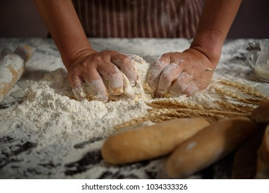 baker prepares bread. baker sprinkle and eggs the dough with flo