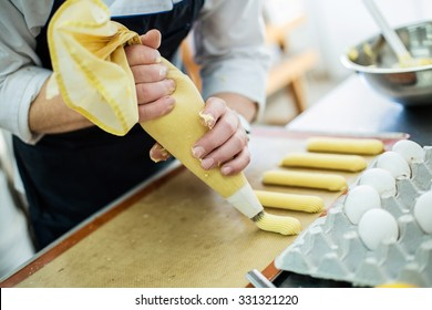 Baker prepares a cake and eclairs