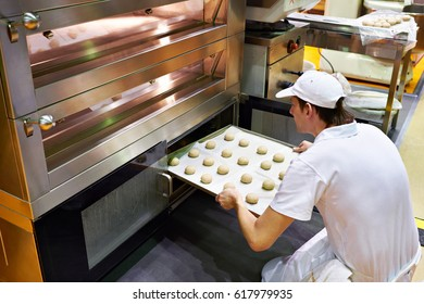 Baker puts a tray of dough balls to bake buns into the oven