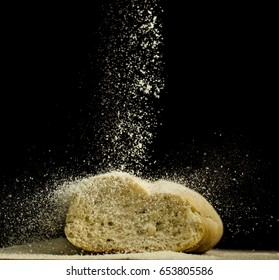 Baker sifting flour over bread bun