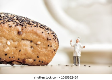?heerful baker standing near bun with poppy seeds.