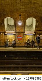 Baker Street, London / UK - January 29 2019:  People waiting for train on Baker Street underground station with underground logo and Baker street signs