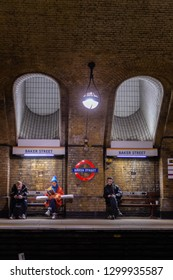 Baker Street, London / UK - January 29 2019:  People waiting for train on Baker Street underground station platform with underground logo and Baker street signs