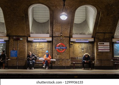 Baker Street, London / UK - January 29 2019:  People waiting for train on Baker Street underground station platform with underground logo and Baker street signs