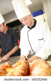Baker with students in kitchen making pastries