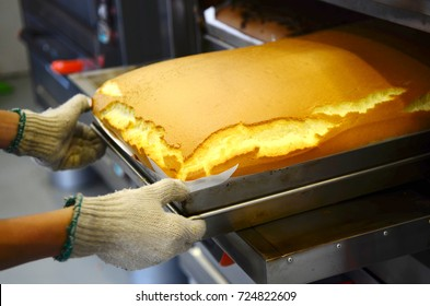 Baker taking out taiwanese traditional sponge cake from the oven