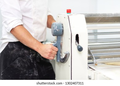 Baker using dough sheeter machine to produce croissants dough at the bakery .