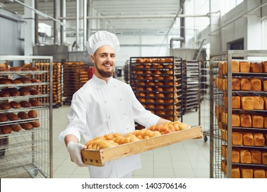 Baker in white uniform with trays of fresh bread costs in bakery.