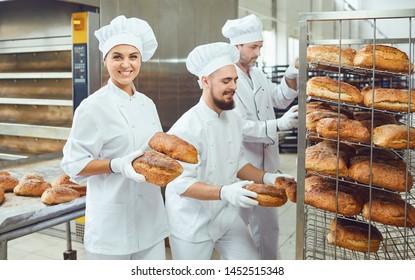 A baker woman holds fresh bread in a bakery.
