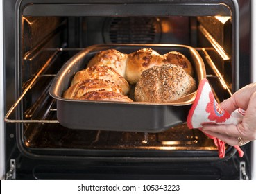 Baker's hand with potholder next to metal cookie sheet with bread in the oven