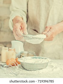 The baker's hands knead the dough for homemade bread, sift flour, rustic style