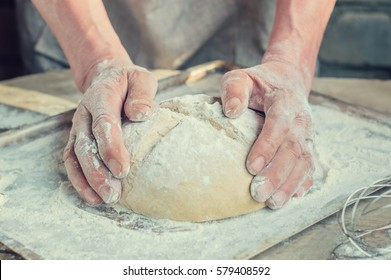 Baker's hands and wheat bread before baking. rustic style