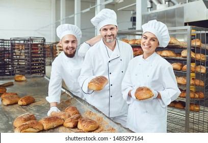 Bakers smiling holding fresh bread in their hands in a bakery