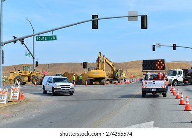 BAKERSFIELD, CA - APR 29, 2015: Traffic must be managed while heavy equipment is employed to lay new sewer pipe across busy State Route 178.