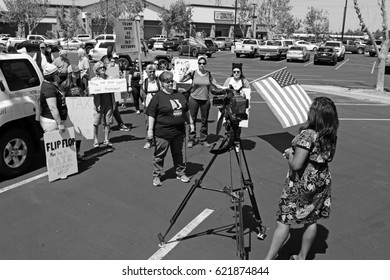 BAKERSFIELD, CA - APRIL 15, 2017: A local protest rally and march is held, trying to influence President Trump to release his tax returns. Reyna Harvey prepares to interview a woman for KBAK TV.
