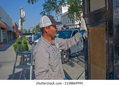 BAKERSFIELD, CA - AUGUST 16, 2018: Hector, a city employee, is busy cleaning graffiti from a downtown kiosk.