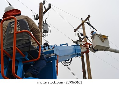BAKERSFIELD, CA - DECEMBER 21, 2014: An electrician works from the basket of a man lift during the high voltage cutover phase of a wood pole replacement by the local utility company.