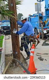 BAKERSFIELD, CA - DECEMBER 21, 2014:  A lineman with spiked boots climbs the pole to assist in the power cutover during a wood pole replacement by the local power company.