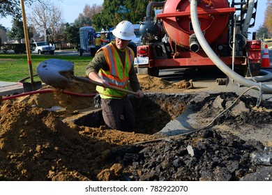 BAKERSFIELD, CA - DECEMBER 28, 2017: Josh McCartney digs out soil from around an underground pipe. The water service company is replacing a damaged section.
