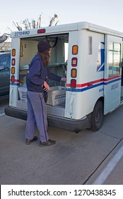 BAKERSFIELD, CA - DECEMBER 29, 2018: An unidentified postal carrier sorts through the mail on his vehicle prior to delivery.