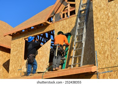 BAKERSFIELD, CA - FEBRUARY 12, 2015: Construction workers apply particle board to the exterior of a two story house, part of the Parkview Cottages low income redevelopment project.